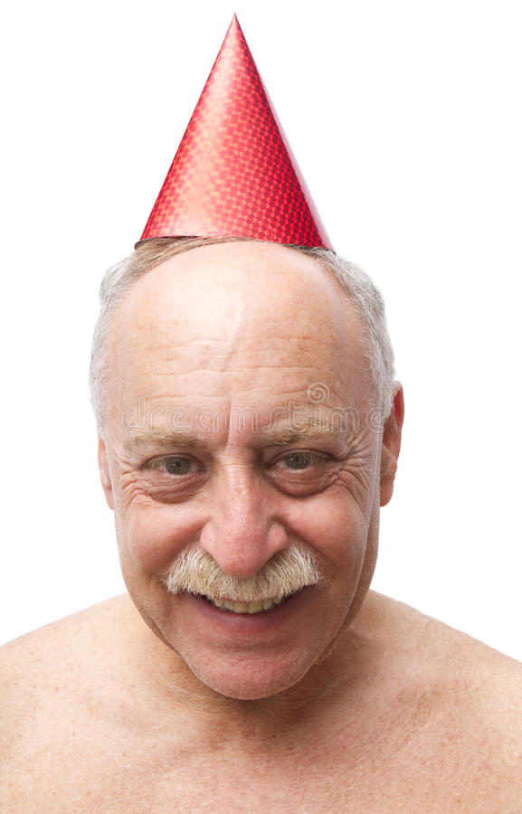 Birthday Boy. A balding man, isolated on a white background, wears a red birthday hat royalty free stock photography