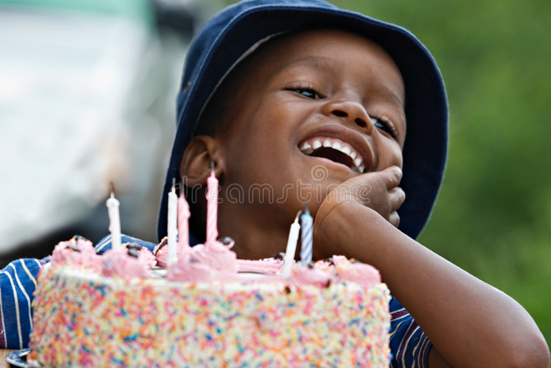 Birthday boy. African American birthday boy behind multicolor cake royalty free stock image