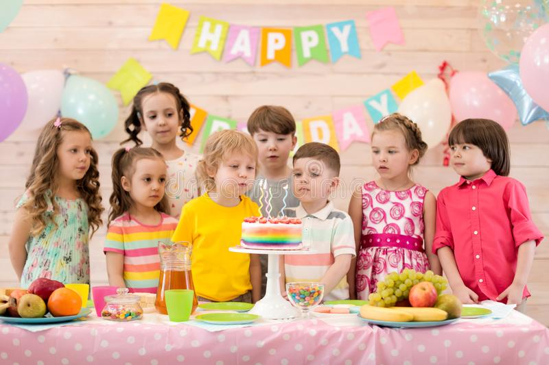 Birthday boy blows festival candles on cake together with friends stock photos