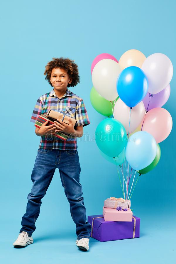 Birthday Boy on Blue. Full length portrait of cheerful African-American boy holding presents posing against blue background, Birthday party concept royalty free stock photos