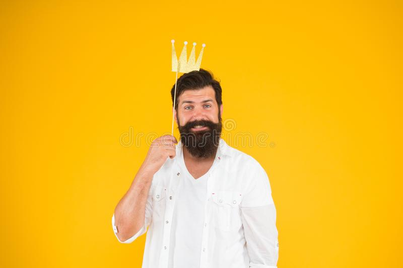 Birthday boy. Guy in yellow background posing with booth props. Photo booth fun. Bearded man king costume party. Handsome bearded guy king. King of party royalty free stock photo