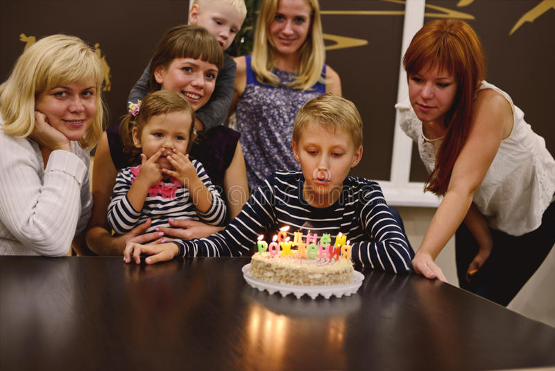 Birthday. Boy and his family in his birthday in light of candles stock image