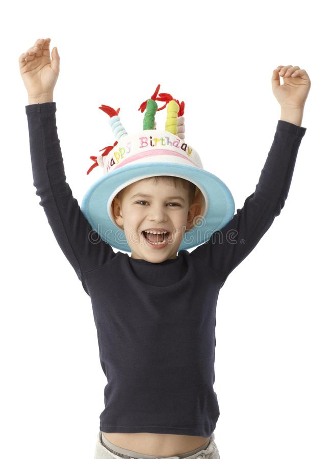 Birthday boy smiling happy in funny hat. Little boy smiling happy on his birthday, wearing birthday cake hat with candles stock images