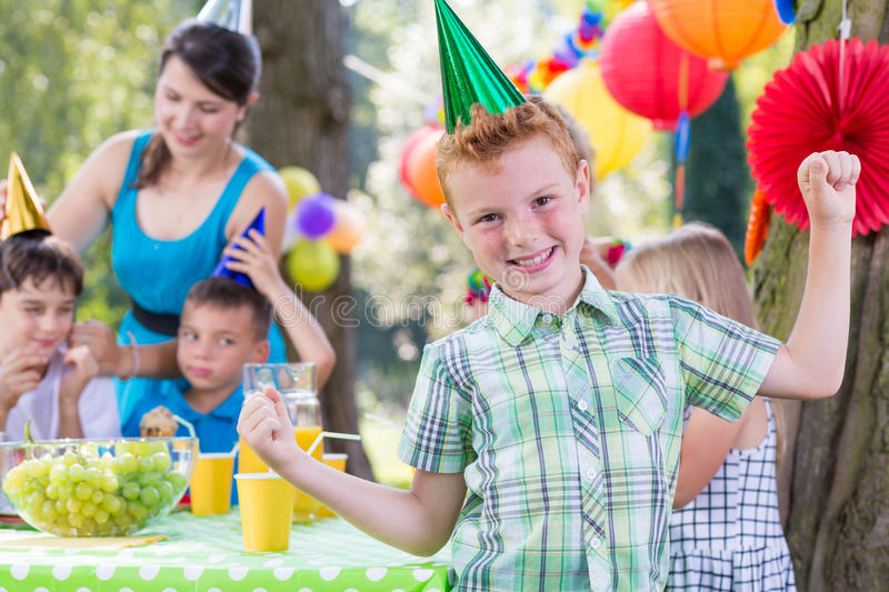 Birthday boy wearing party hat. Happy birthday boy wearing party hat, kids entertainer in background royalty free stock photos