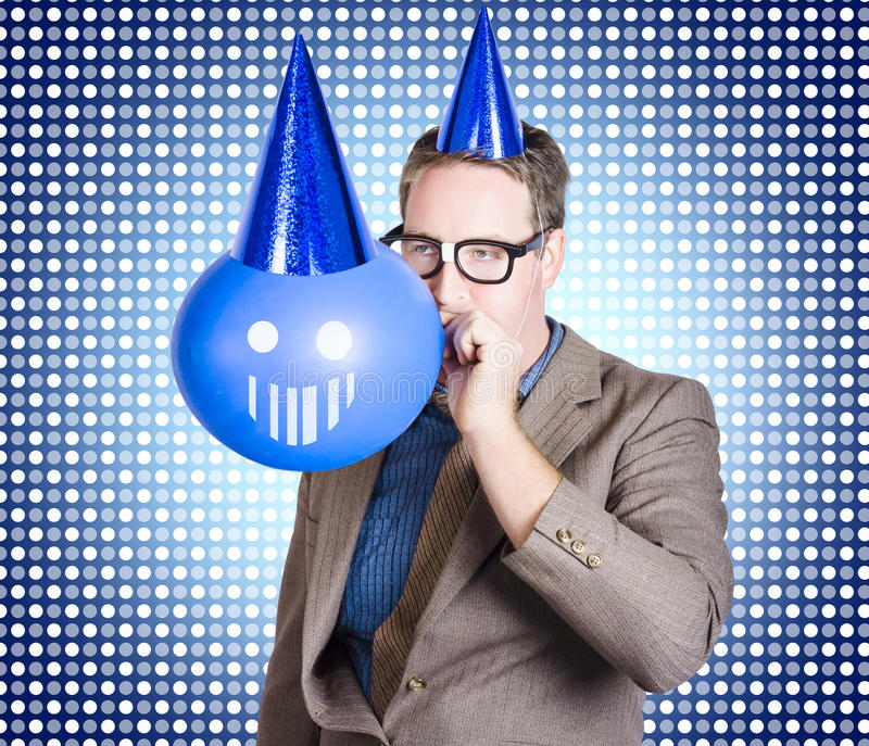 Birthday businessman blowing up smiling balloon