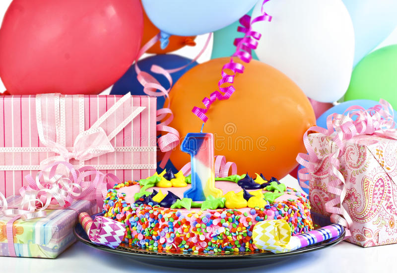 Birthday cake for 1 year old. Pretty pink birthday cake with the number 1 candle. Cake is surrounded by gifts, party balloons, poppers and ribbons stock image