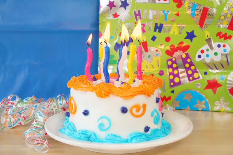 Birthday Cake. With candles lit and packages in the background with room for your text royalty free stock image