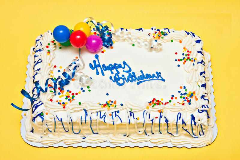 Birthday Cake. Large decorated Birthday cake with white icing, sprinkles, ribbons, balloons stock images
