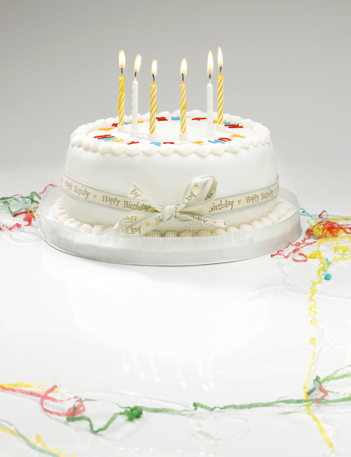 Birthday cake. A white birthday cake with light candles and streamers royalty free stock photography