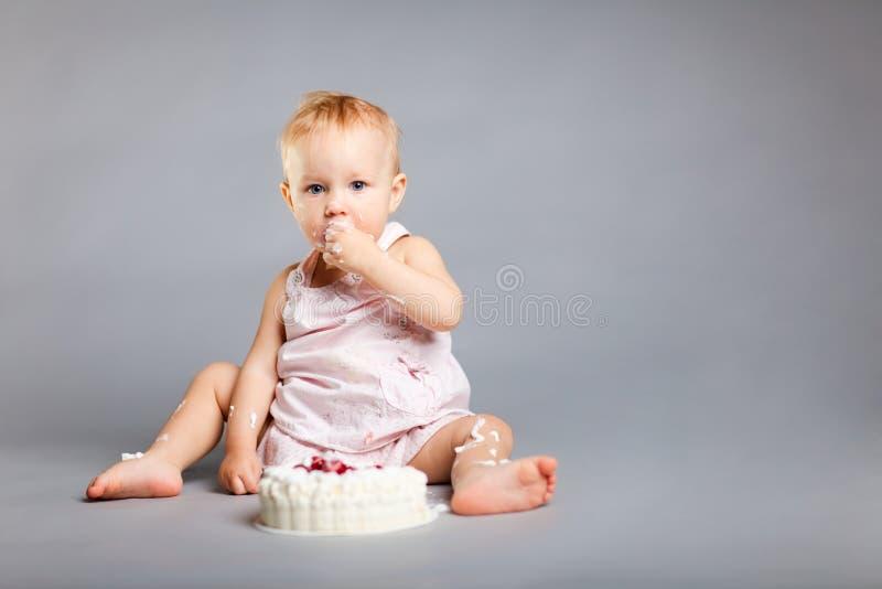 Birthday cake. Cute little girl eating her first birthday cake stock photo