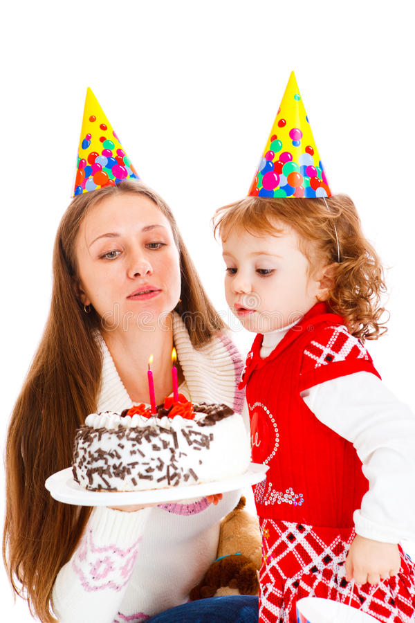 Birthday cake. Girl blowing at her birthday cake royalty free stock photography