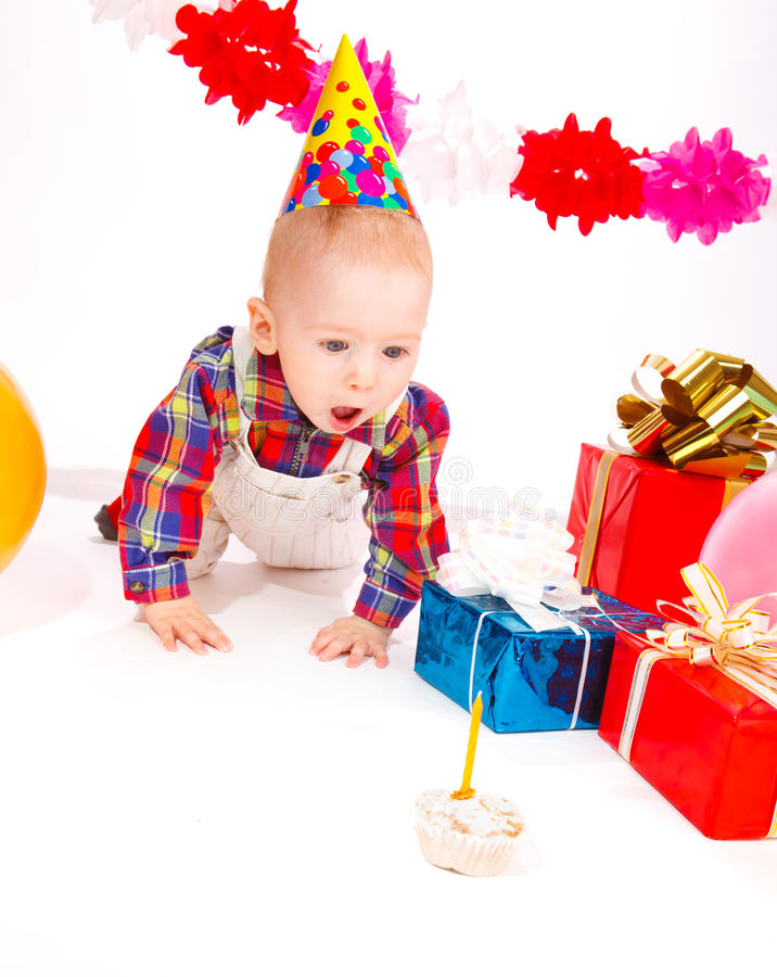 Birthday cake. Baby in a party hat looks at the birthday cake with surprise stock photos