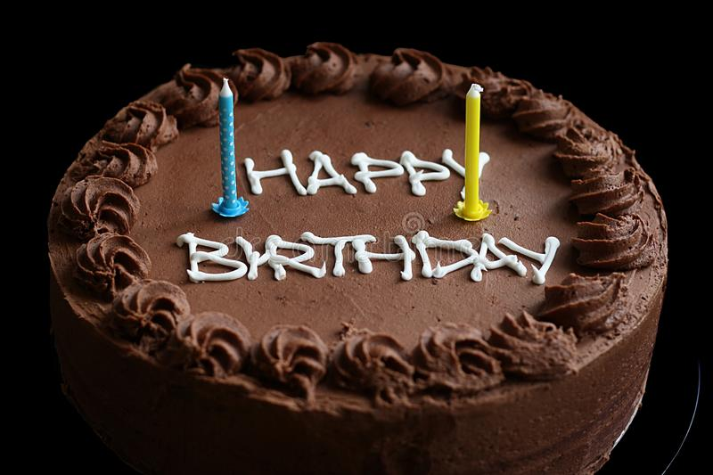 Birthday Cake. Chocolate birthday cake on black background with candles stock image
