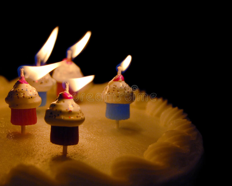 Birthday Cake. Lit birthday cake with little cupcake shaped candles stock photography