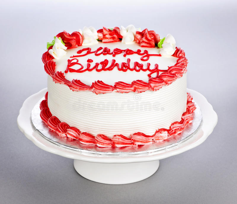 Birthday cake. With white and red icing on plate royalty free stock image