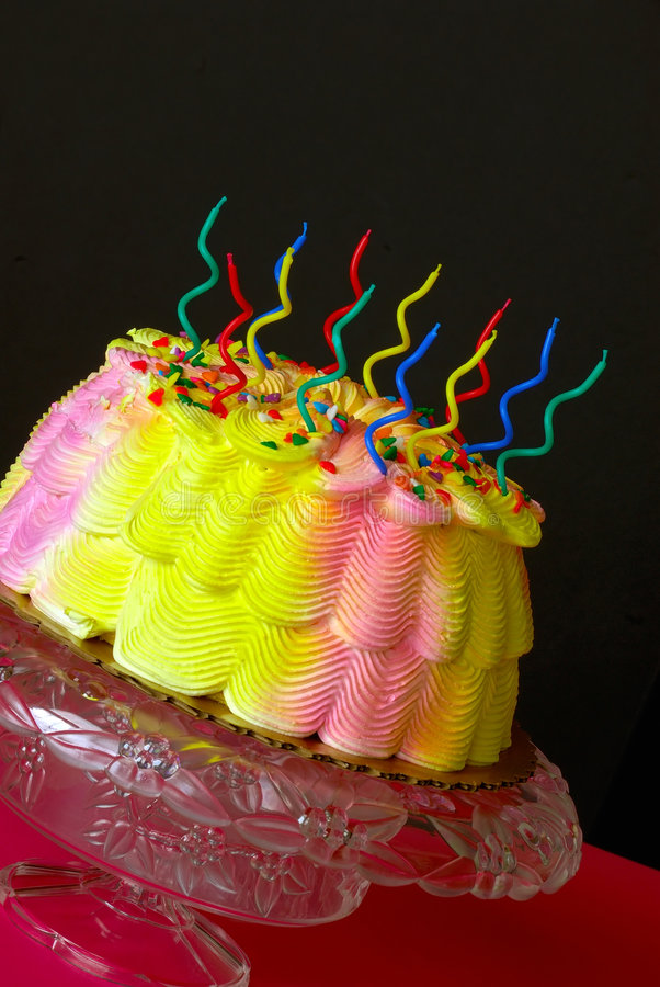Birthday Cake. A pink and yellow iced  with unlit swirly candles sits in front of a black background royalty free stock images