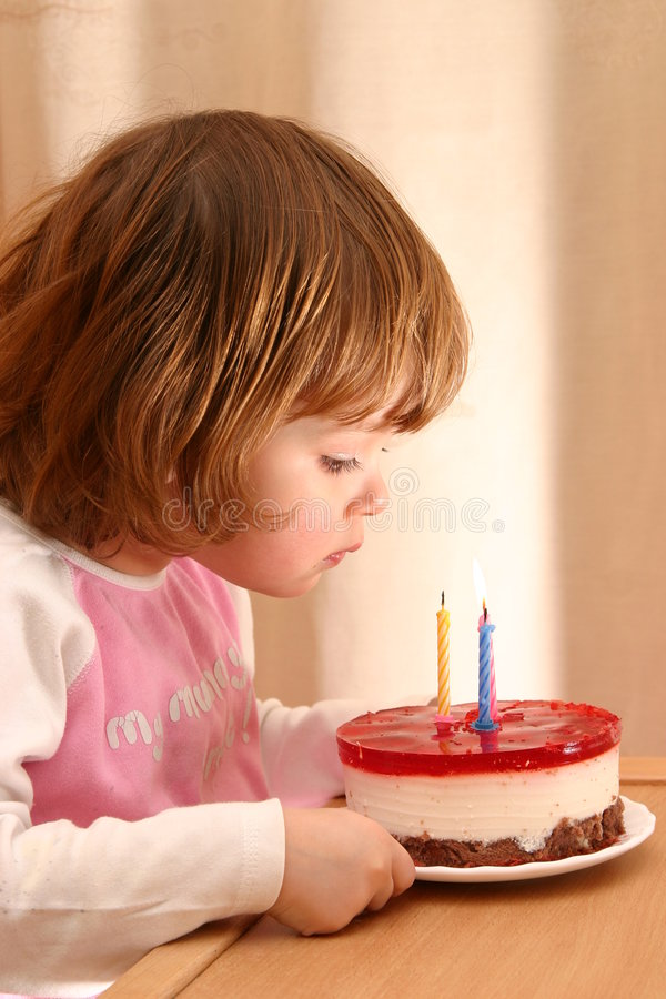 Birthday cake. Little girl and her birthday cake with candles stock images
