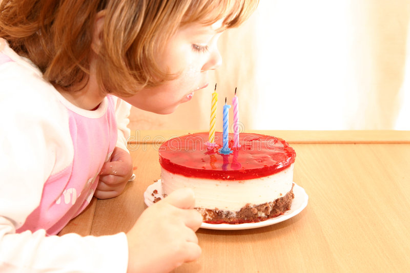Birthday cake. Little girl and her birthday cake with candles stock photography