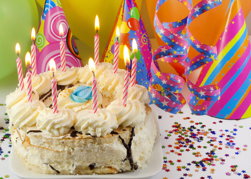Birthday cake. Happy birthday cake with candles and balloons against colorful bokeh background royalty free stock photos