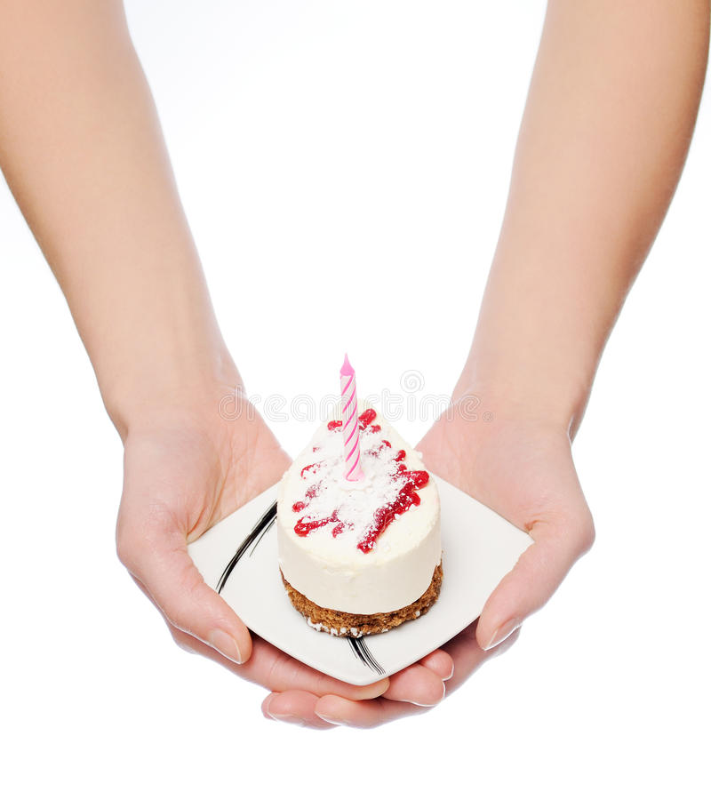 Birthday cake. Female hands keep birthday cake with candle. Isolated on white royalty free stock images