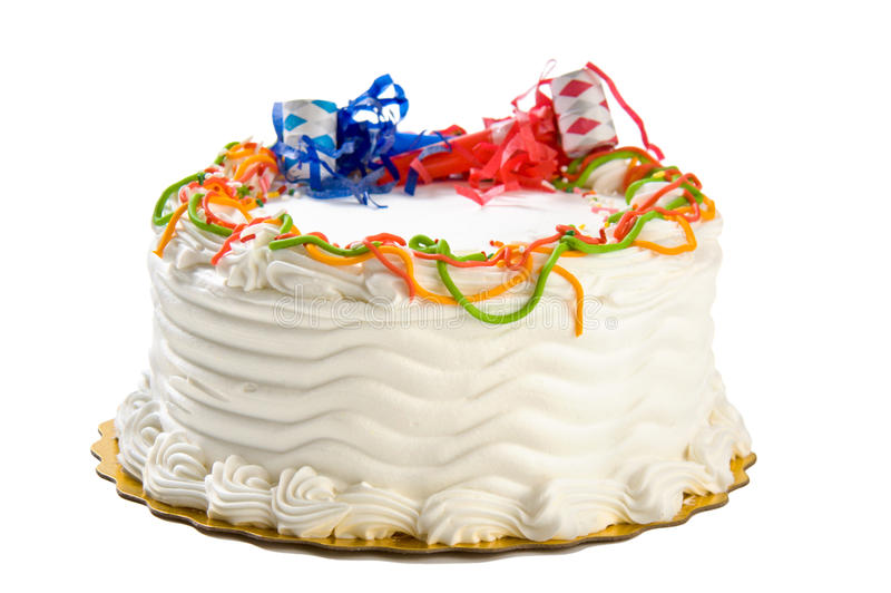 Birthday cake. A plain birthday cake topped with noisemakers isolated on white stock images