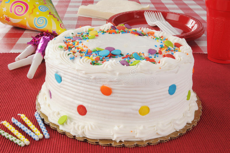 Birthday Cake. A birthday cake with party streamers, candles and plastic plates stock images