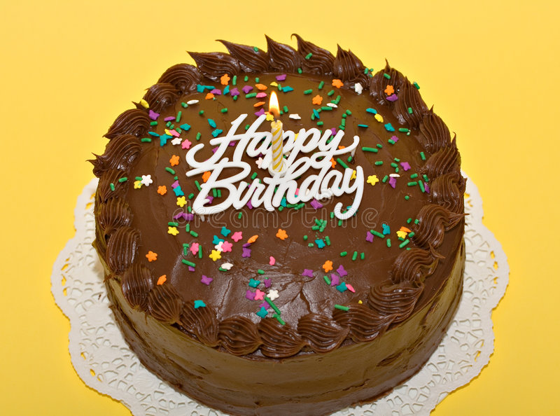 Birthday Cake. Chocolate birthday cake with lit candle and sprinkles royalty free stock image
