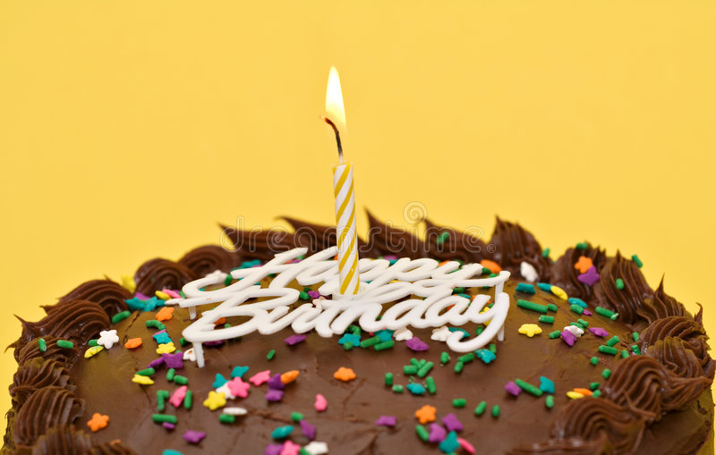 Birthday Cake. A chocolate birthday cake with a lit candle, words and sprinkles royalty free stock images