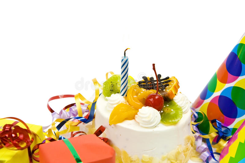 Birthday cake. White birthday cake with fruit and blue candle royalty free stock photos