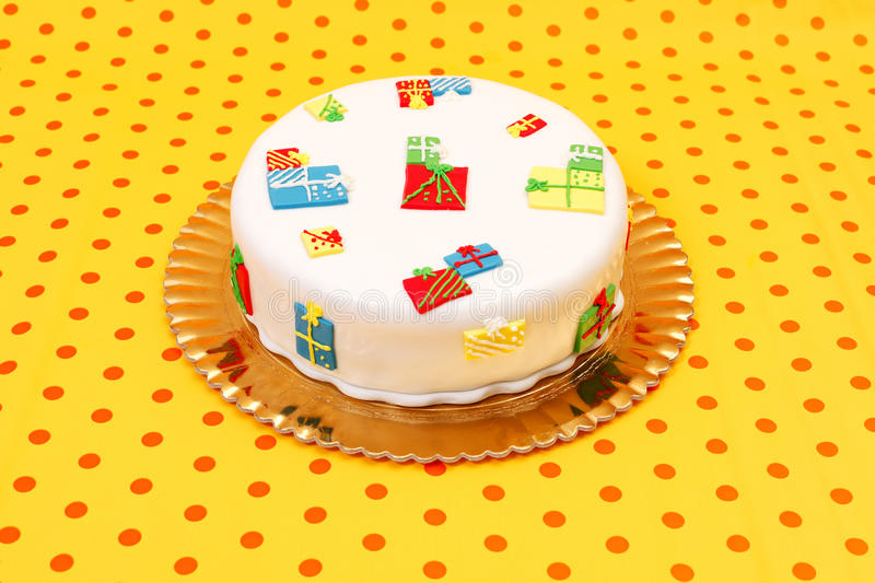 Birthday cake. White birthday cake with marzipan ornaments on dotted orange background royalty free stock photography