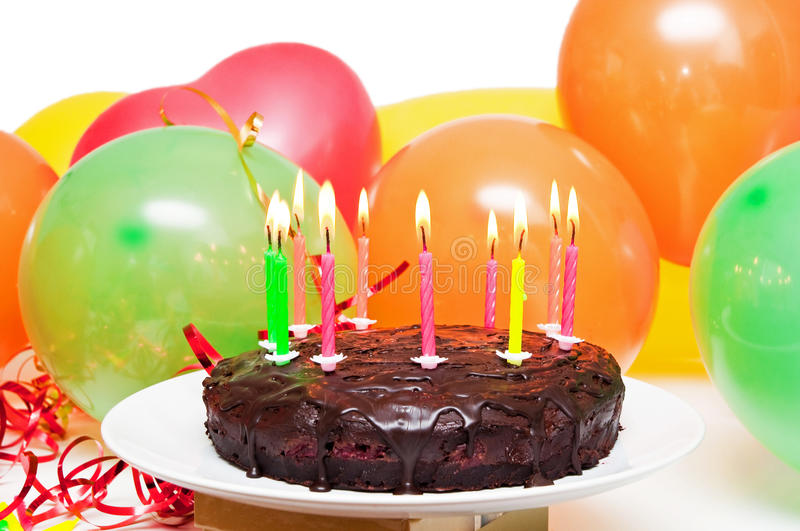 Birthday cake. With burning candles and party balloons stock photography