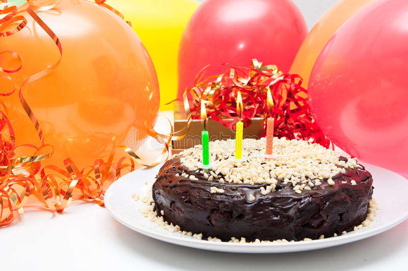 Birthday cake. With burning candles and party balloons royalty free stock image