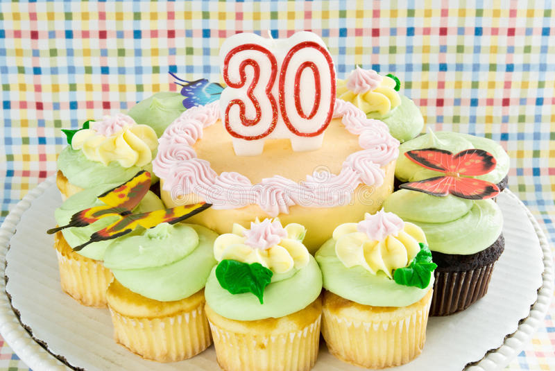 Birthday cake. With unlit 30 year candle. cake is surrounded by chocolate and yellow cupcakes. Ornate decorations include butterflies and flowers made from royalty free stock images