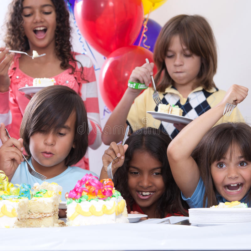 Birthday Cake. Five multi-ethnic kids eating cake at a birthday party royalty free stock photography