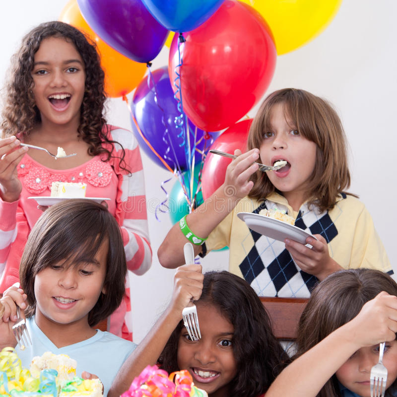 Birthday Cake. Five multi-ethnic kids eating cake at a birthday party stock photos