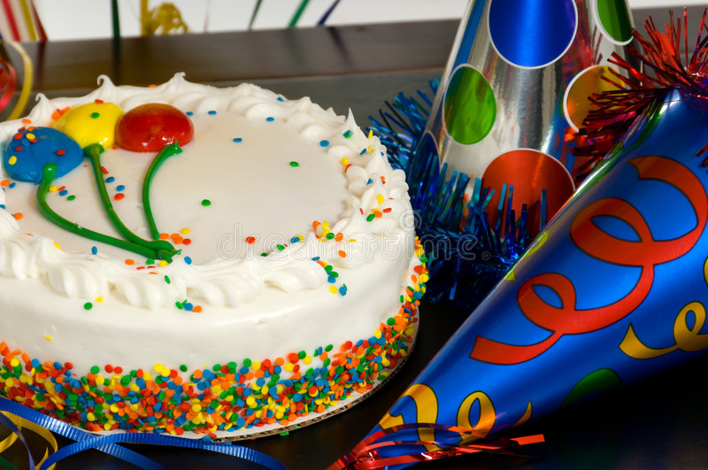 Birthday Cake. With balloons on the icing and party hats on a table at a birthday party stock photography
