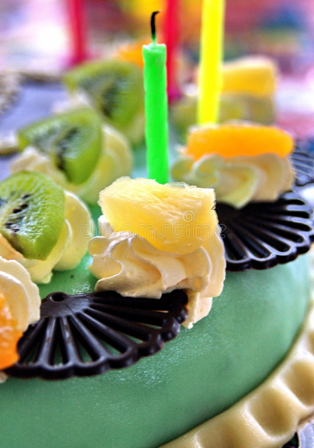 Birthday cake. A colorful birthday cake detail, focus on one of the candles royalty free stock photos