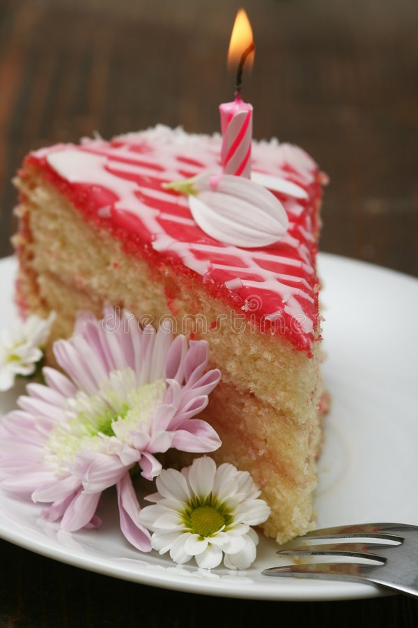 Birthday cake. A slice of a cream cake with birthday candle and flowers stock image