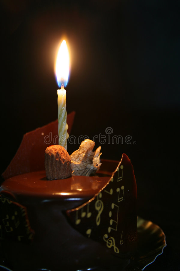 Birthday cake. Chocolate birthday cake with a candle lighted royalty free stock photography