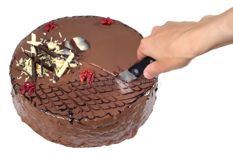Birthday cake. Hand cutting a birthday cake with walnuts and decoration on white background stock photos