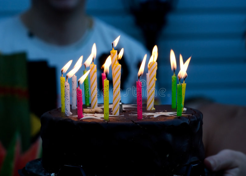 Birthday Cake. With multi colored candles in the hands of the happy family stock photos