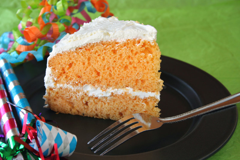 Birthday Cake. Orange colored and flavored birthday cake with vanilla icing along with party favors on the side royalty free stock image