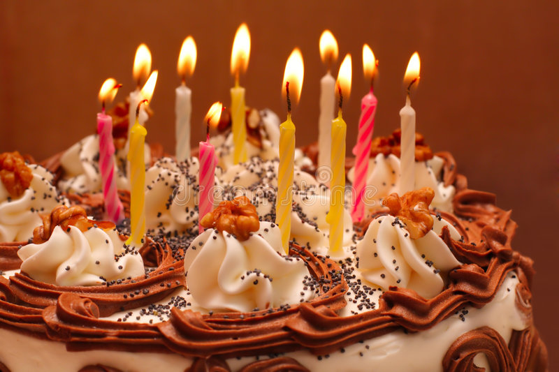 Birthday cake. Lit candles on brown background stock photography