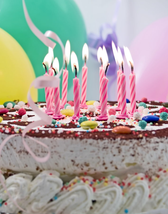 Birthday cake. With eleven burning candles, balloons at background stock photo