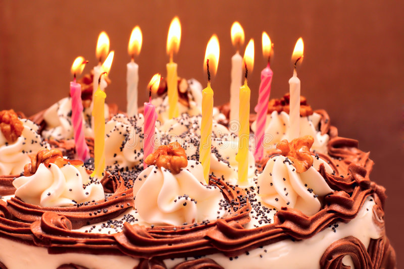 Birthday cake. Lit candles on brown background stock photos