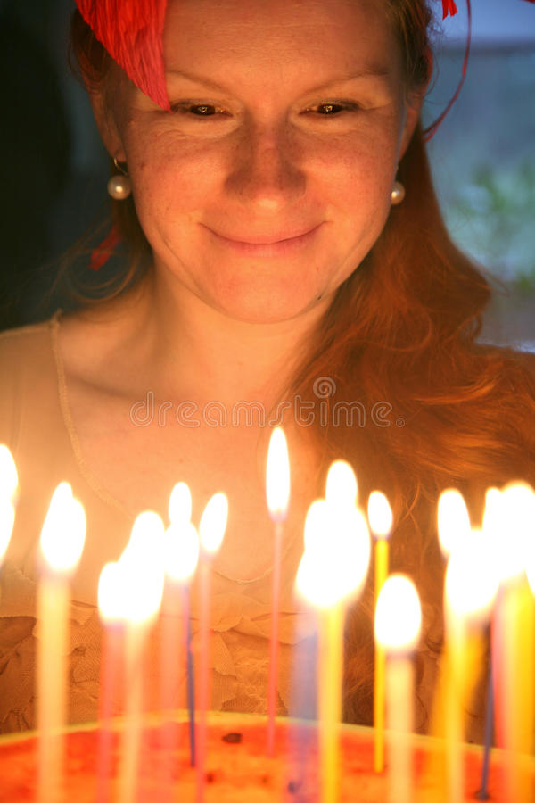 Birthday cake. Smiling and emotionally excited woman with candle lit birtday cake royalty free stock photo