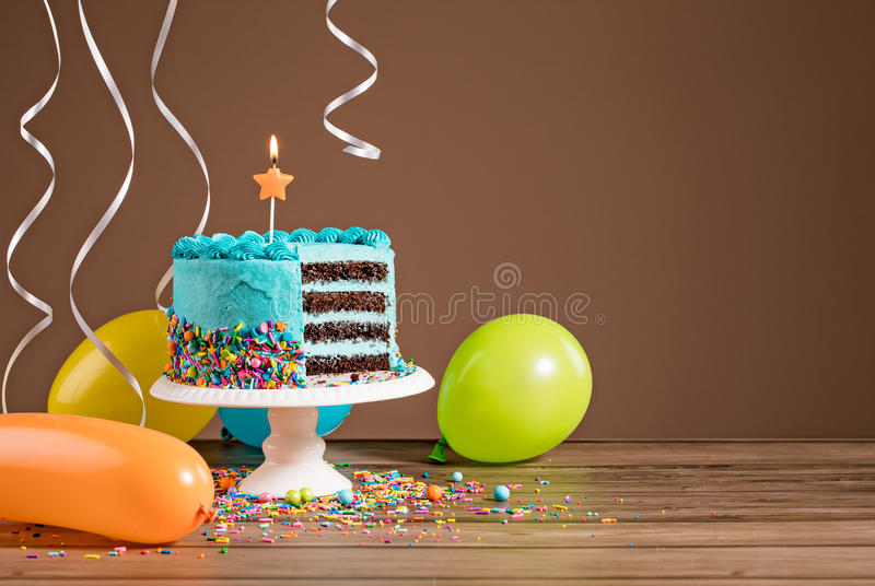 Birthday Cake with Balloons. Chocolate birthday cake with blue buttercream icing and colorful balloons on a brown background stock photography
