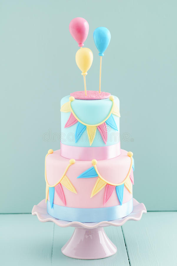 Birthday cake with balloons. Fondant covered pastels coloured birthday cake with buntings and balloons royalty free stock images