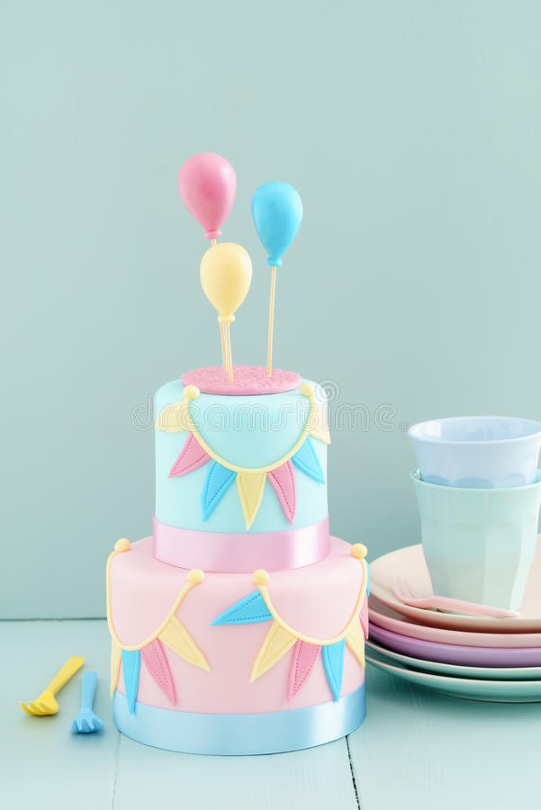 Birthday cake with balloons. Fondant covered pastels coloured birthday cake with buntings and balloons royalty free stock image