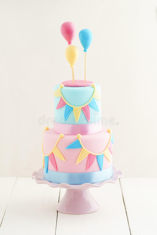 Birthday cake with balloons. Fondant covered pastels coloured birthday cake with buntings and balloons royalty free stock photo